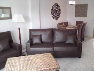 Una vista del salón con dos sofás mas mesa y sillas para 6 personas